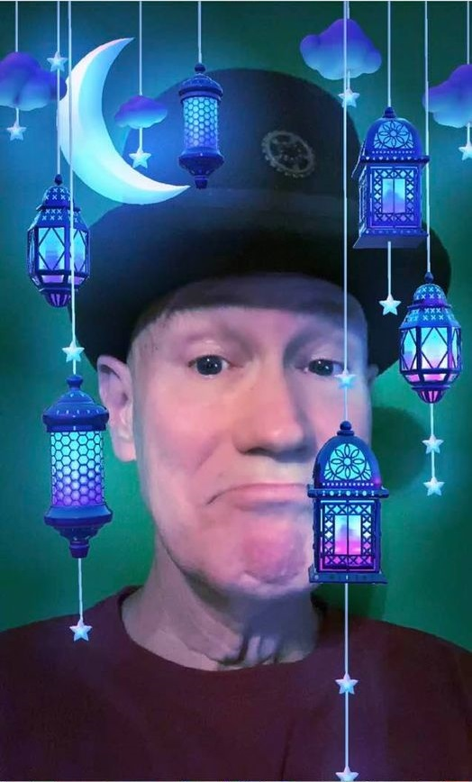 James Carvin wearing a Pamalogy top hat surrounded by lanterns and moonlight.